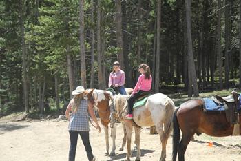 Children receiving horseback instructions from a staff member